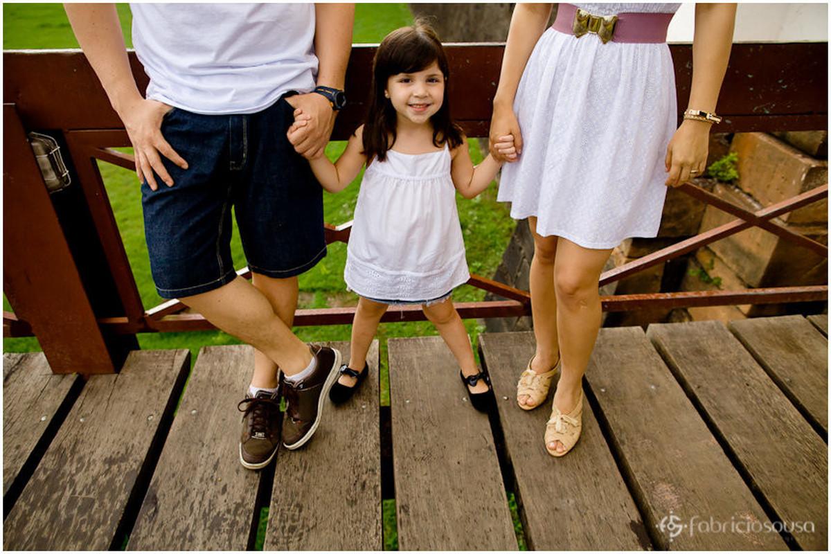 Menina de mãos dadas com os pais