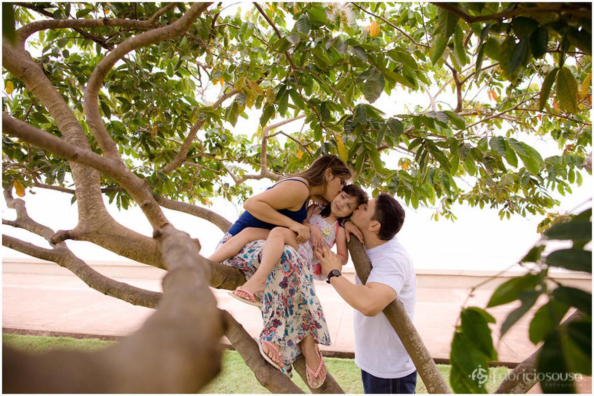 Apoiados em uma árvore, pai e mãe beijam a filha