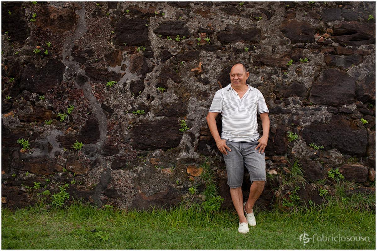 Pai de família escorado em muro de pedra