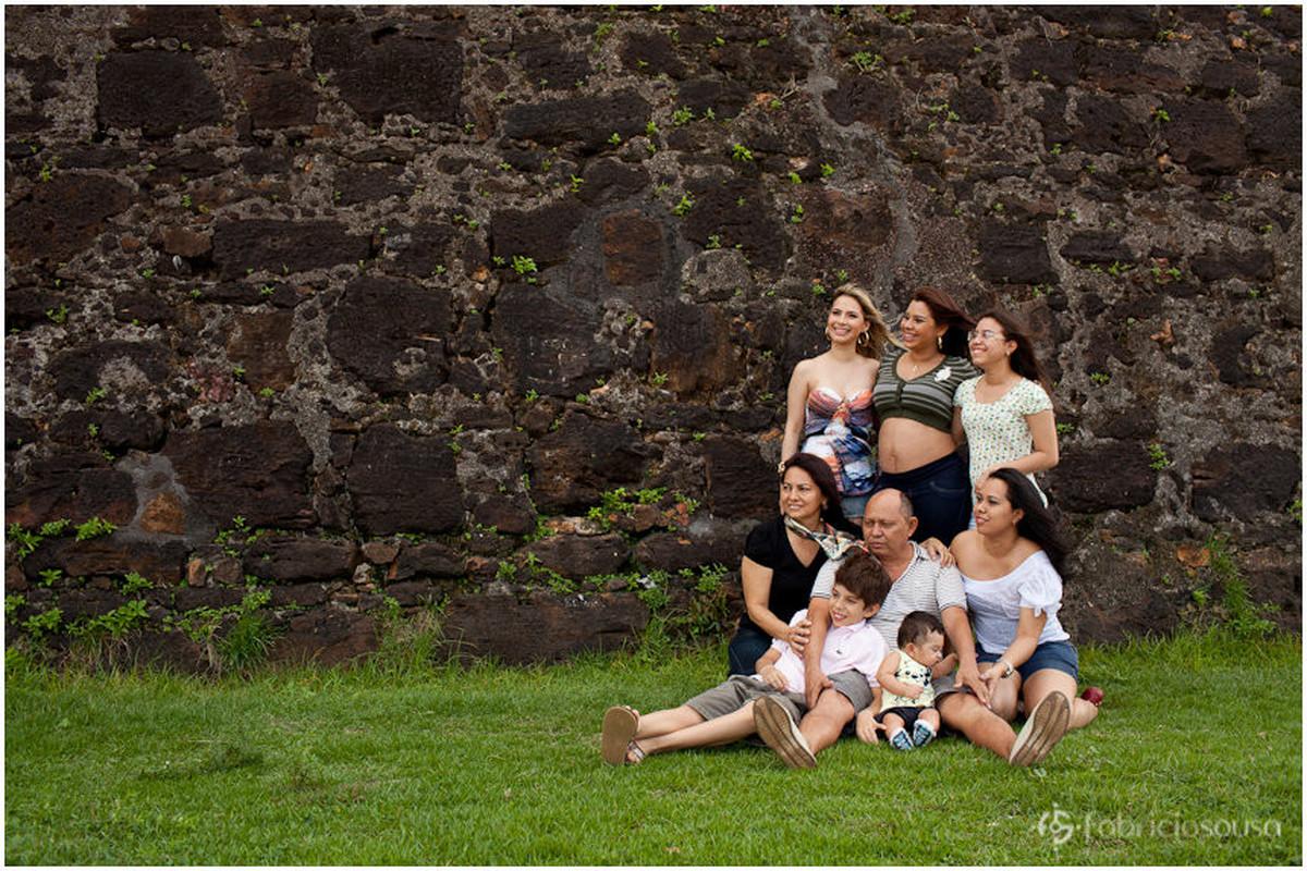 Retrato da família Almeida no gramado verde em frente ao muro de pedra