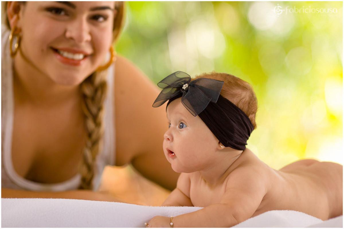 Mariah de bruços com laço preto e a tia junto