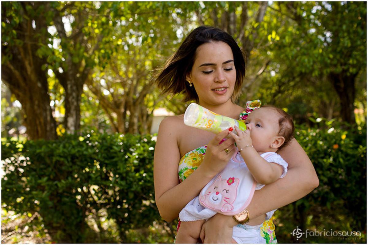 Mãe dando mamadeira para a bebê em seu colo em meio à natureza do parque
