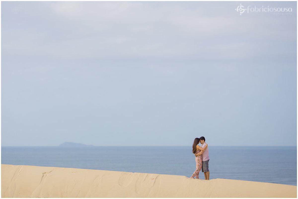 casal namorando nas dunas da joaquina. mar azul de fundo