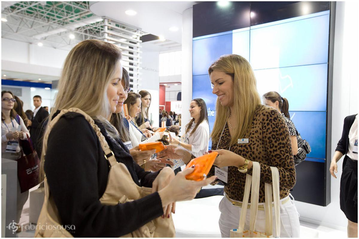 Participantes do congresso de dermatologia recebendo brindes da L'oréal