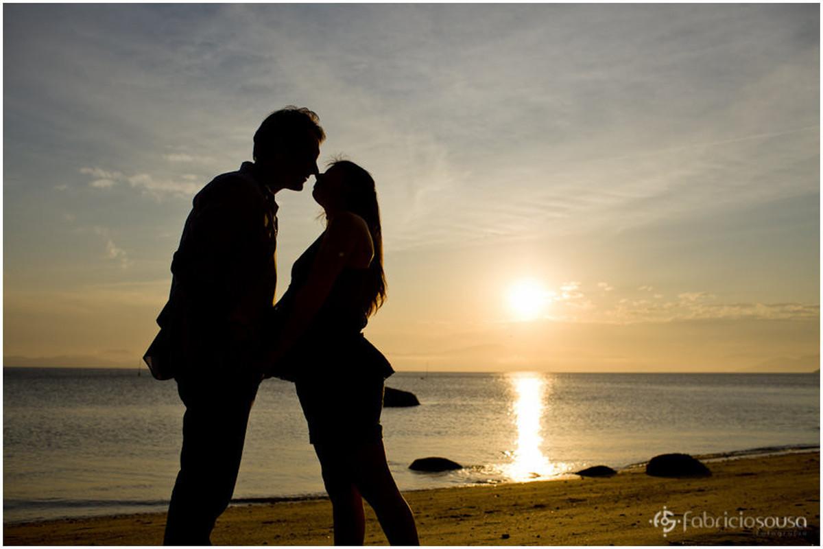 Por do sol e casal gestante na areia da beira do mar