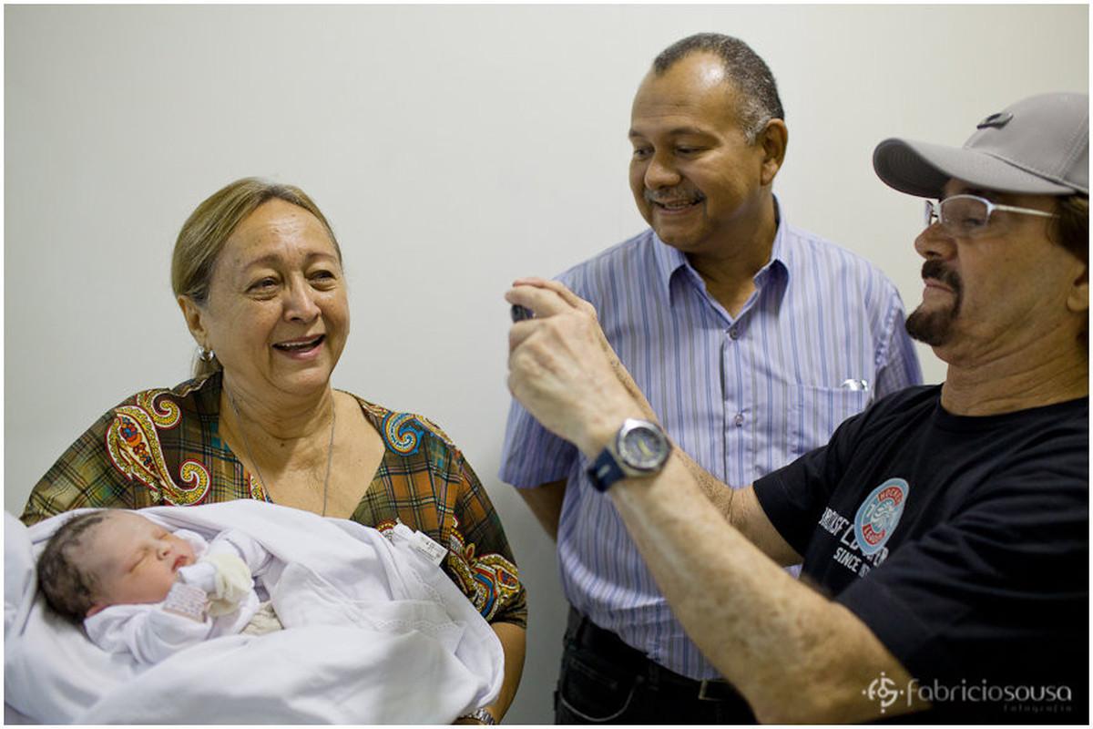 Familiares e parentes tirando fotos com a bebê