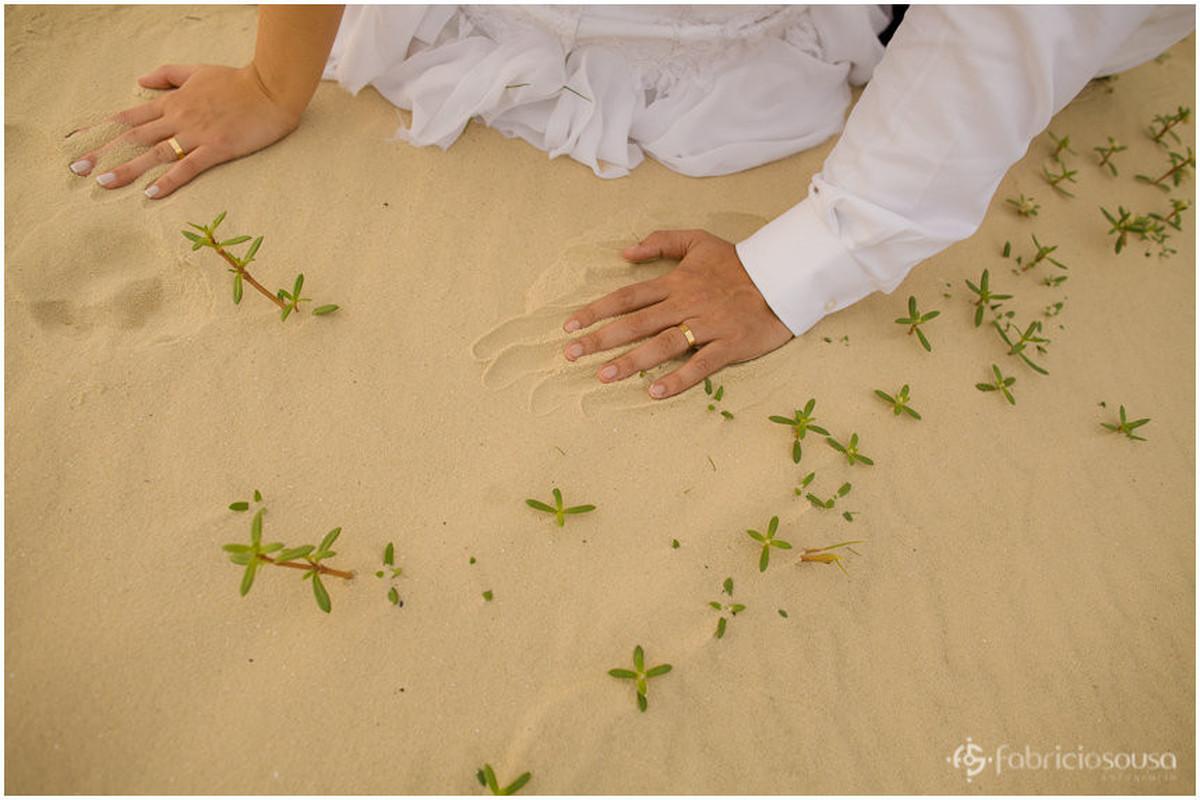 detalhes das mãos na areia durante trash the dress
