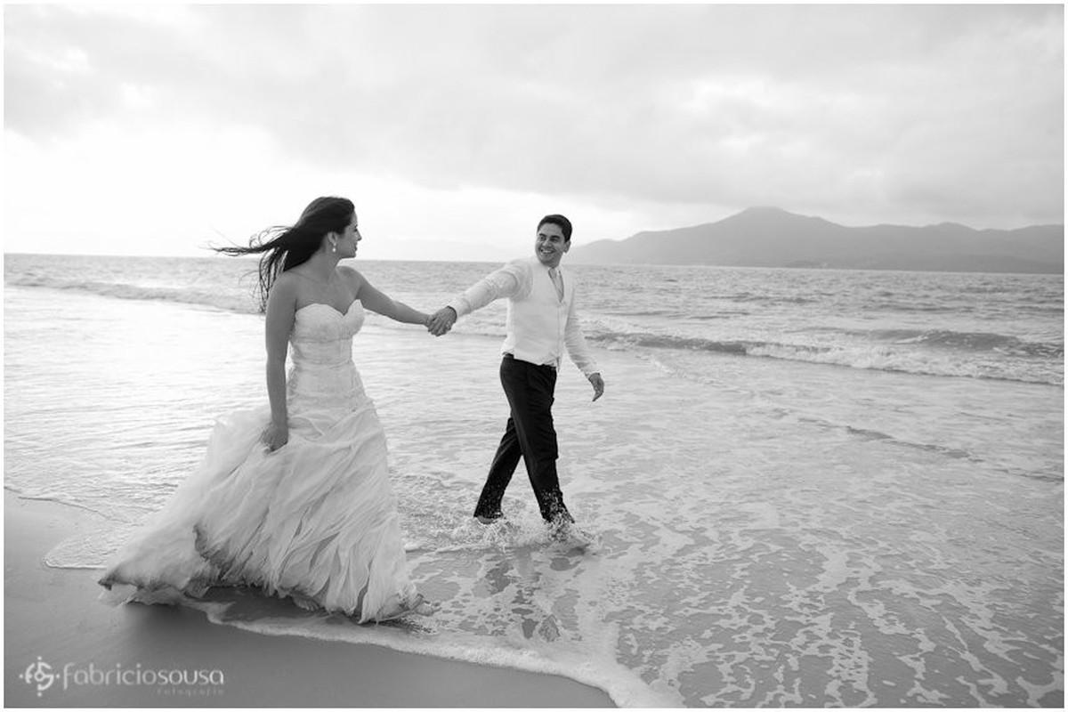 noivos com pés na água na praia da Daniela
