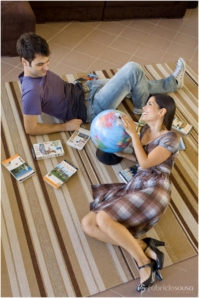 ensaio de casal com livros de viagem e globo terrestre