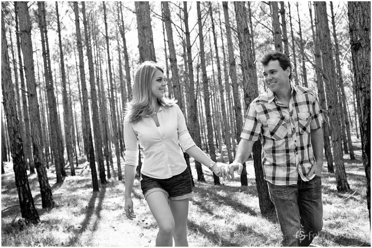 casal caminhando de mãos dadas no bosque