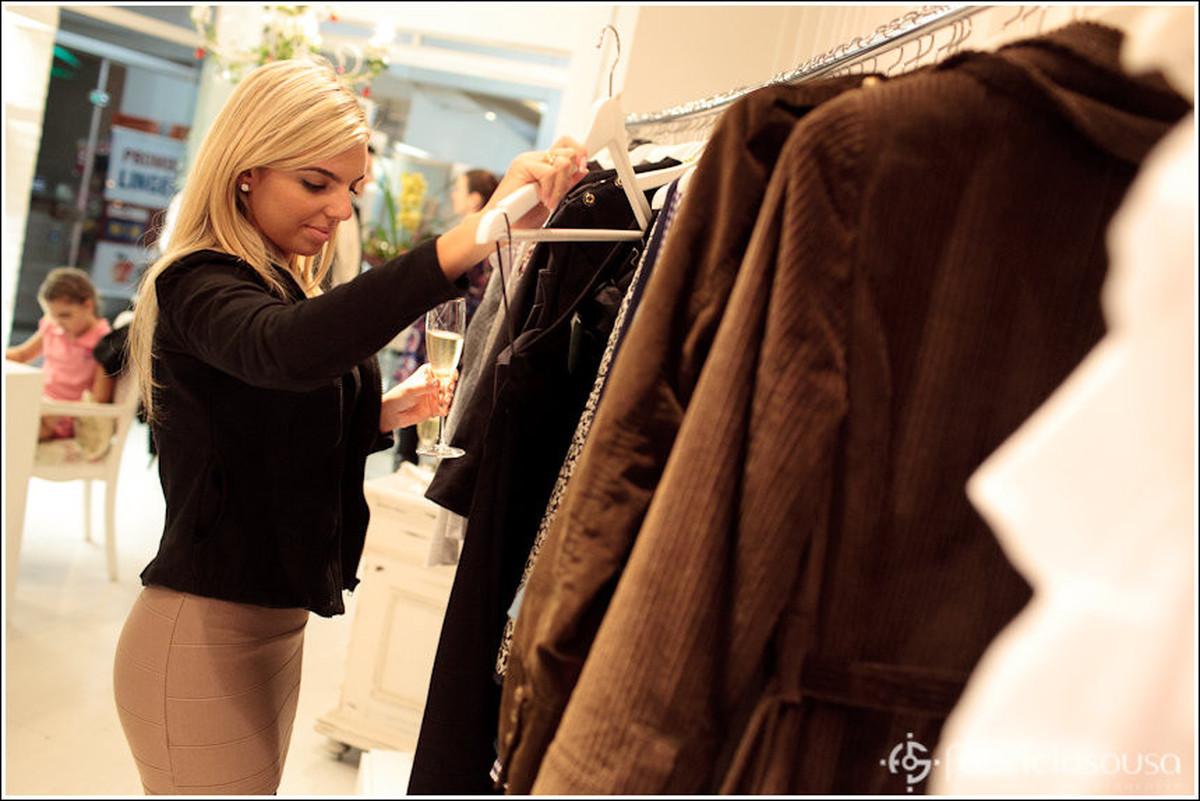 Cliente confere peças de roupas na arara da loja Ana Bauer Exclusive Style