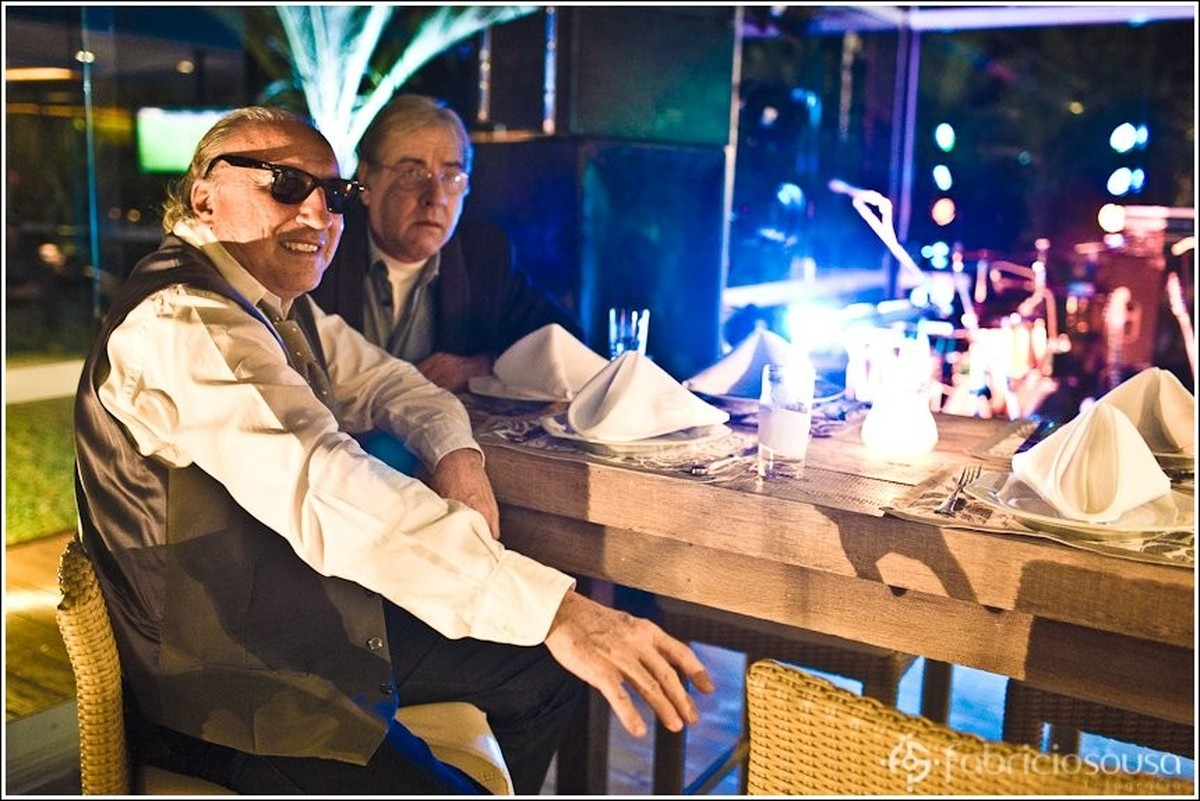 Convidados sentados em mesa alta no salão