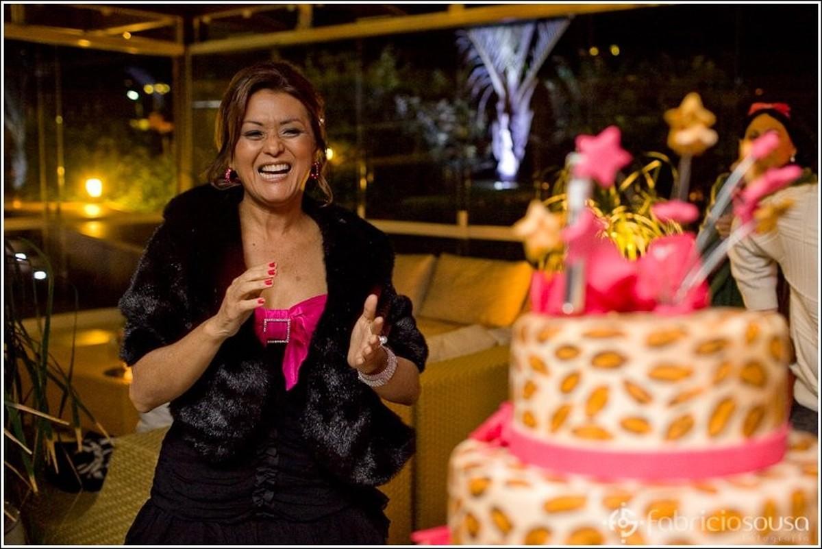 Aniversariante aplaude próxima ao bolo de aniversário