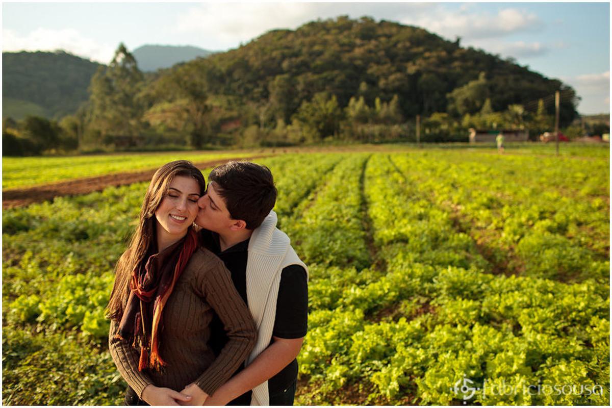 Futuros noivos abraçados e beijo no rosto em frente à plantação no interior do Estado de SC