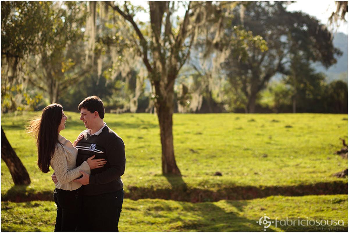 Futuro marido e mulher se abraçam em frente a uma arvore caracteristica da serra