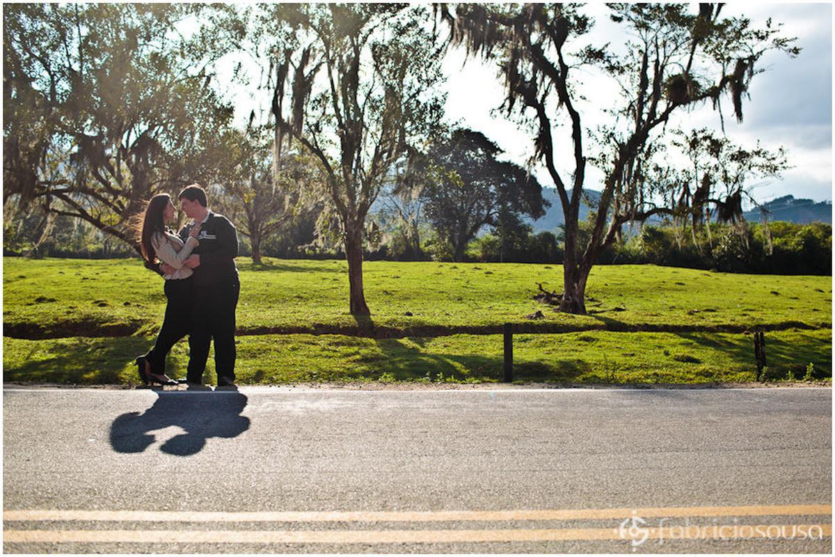 Casal de namorados se abraça na beira da rodovia contra o sol
