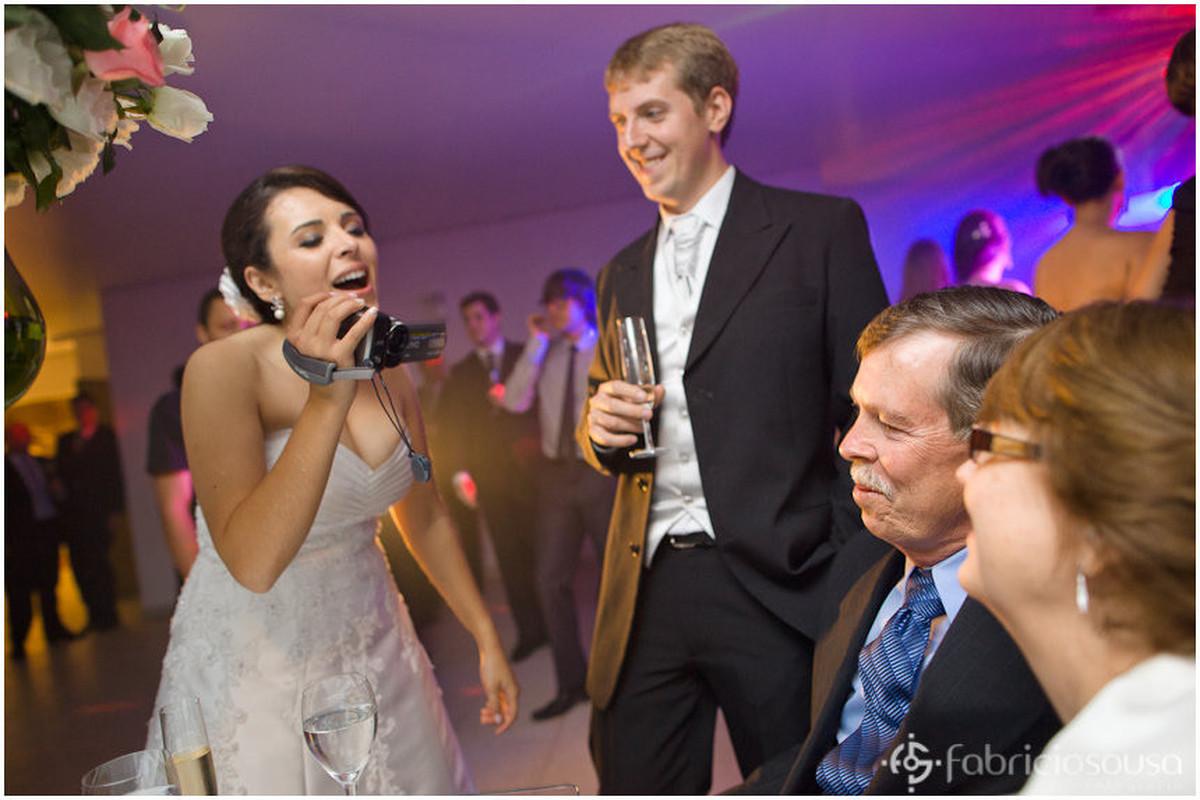 Noiva e noivo filmam os convidados
