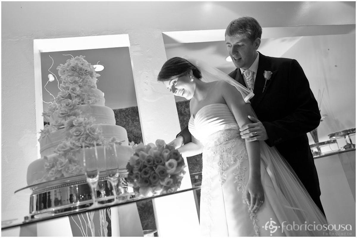 Noiva e noivo cortam o bolo preto e branco