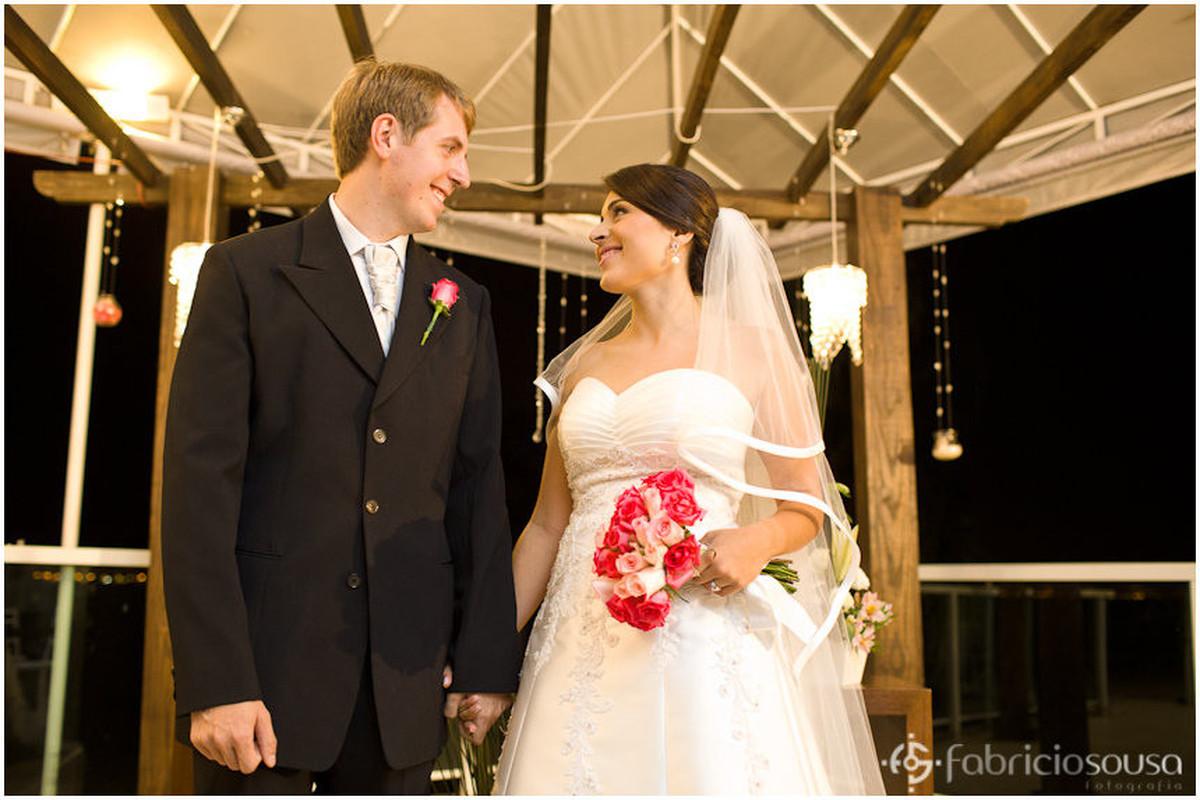 Noivo e noiva se olham de mãos dadas