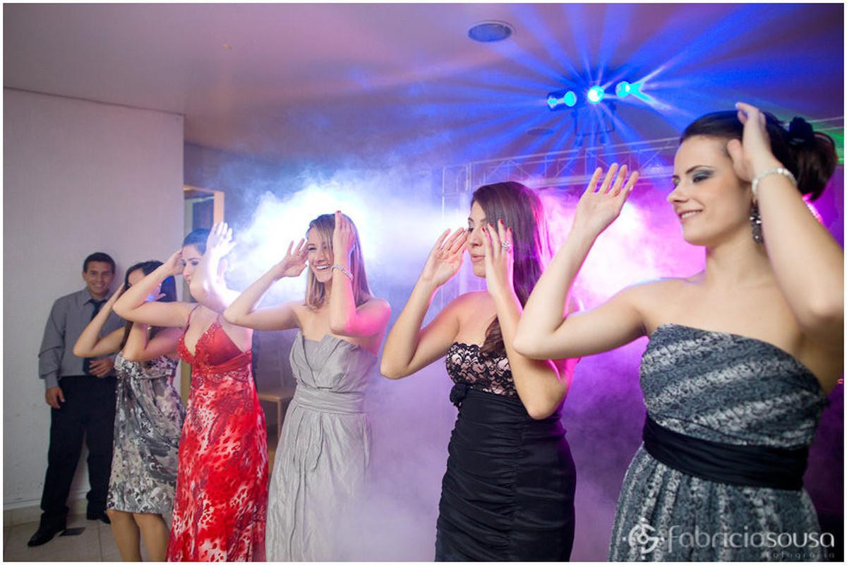 Convidadas alinhadas dançam coreografia na pista de dança da festa