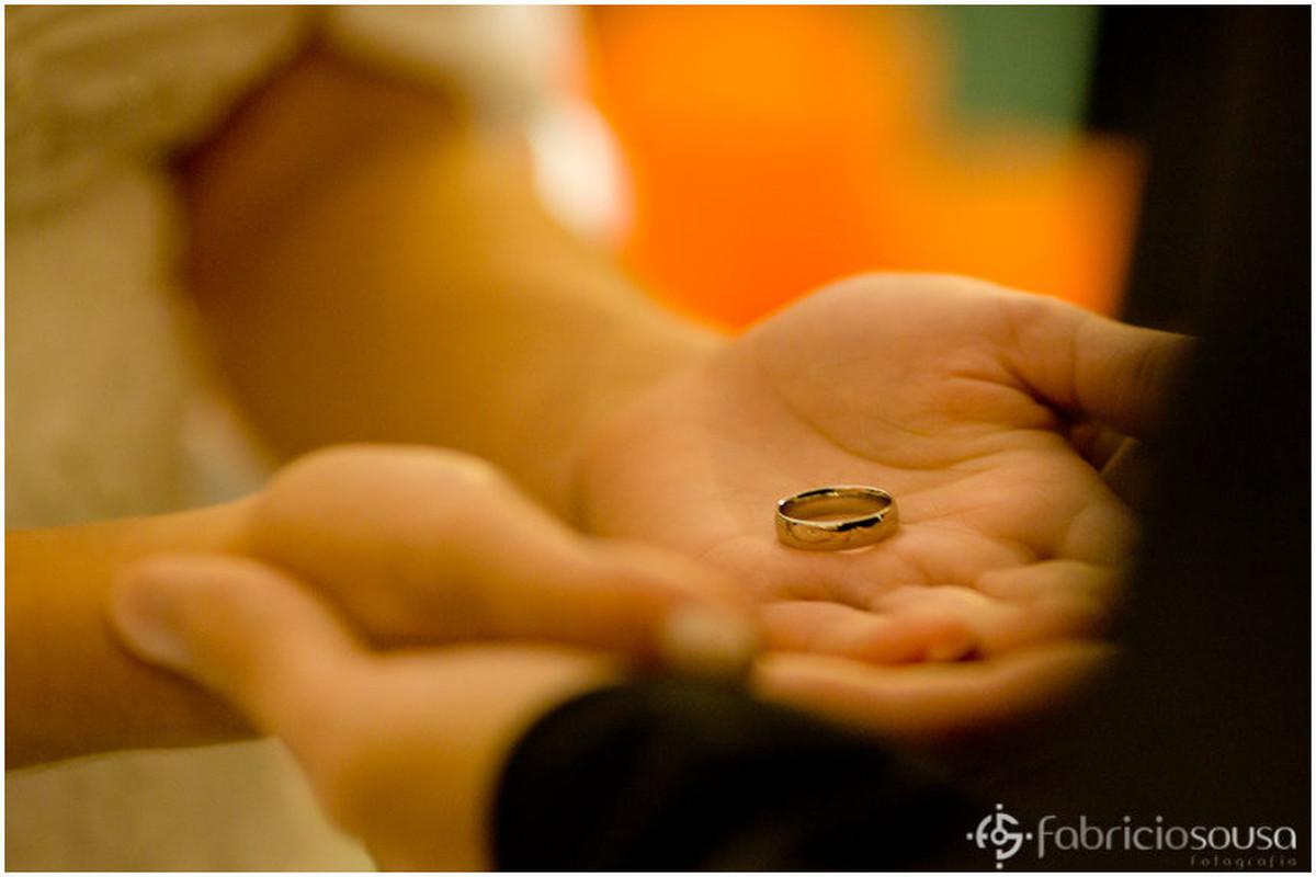 Close nas mãos do casal de noivos que recebem as alianças