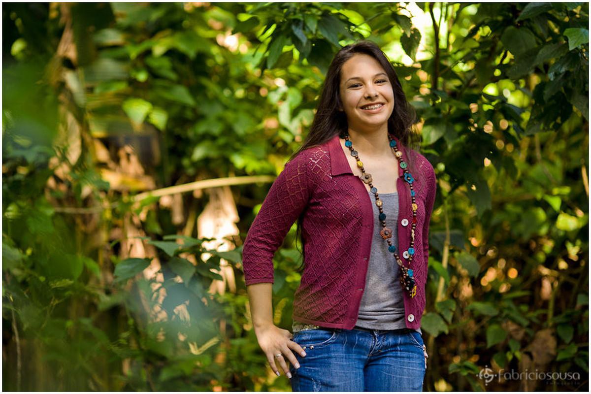 Jovem de 15 anos sorri para foto em meio a vegetação esverdeada
