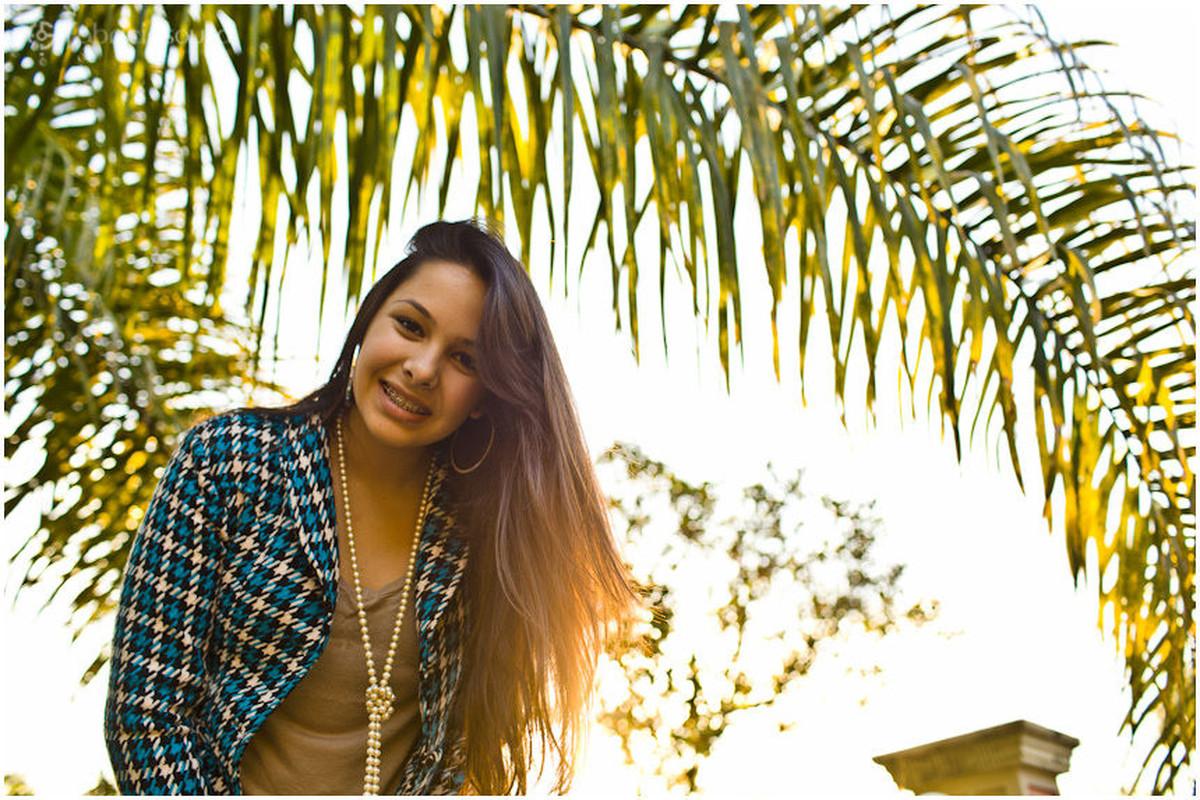 Jovem sorri para foto no por do sol