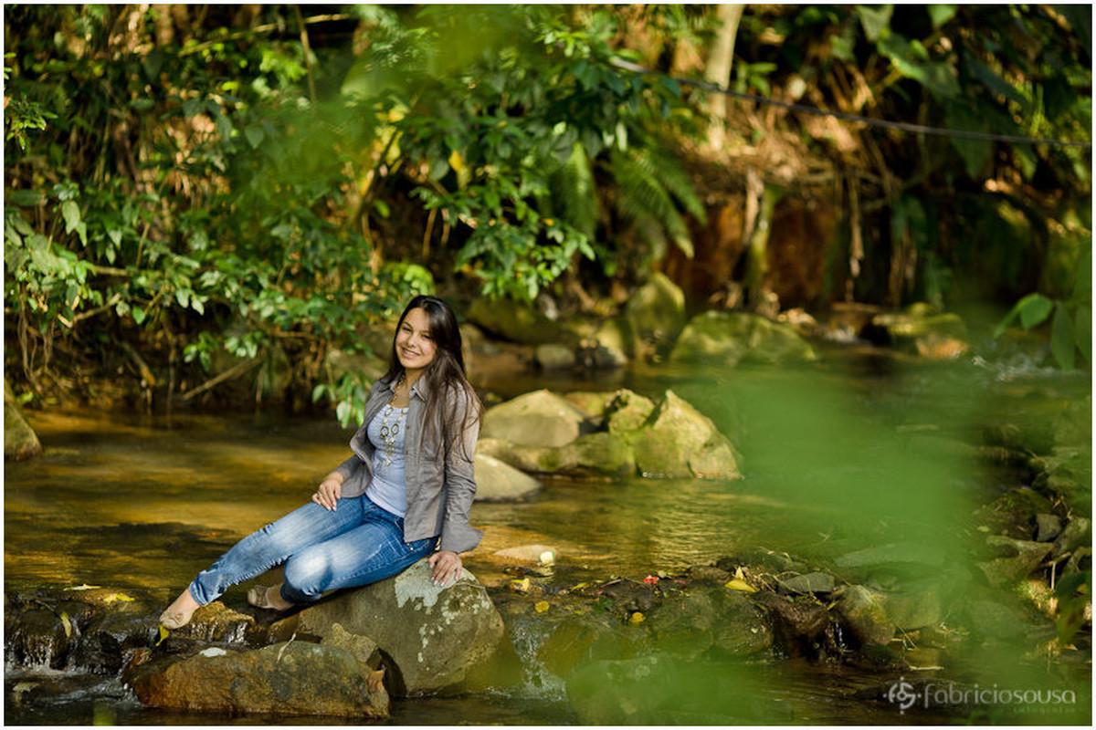 Menina-mulher sentada na pedra na beira do lago em ensaio fotográfico