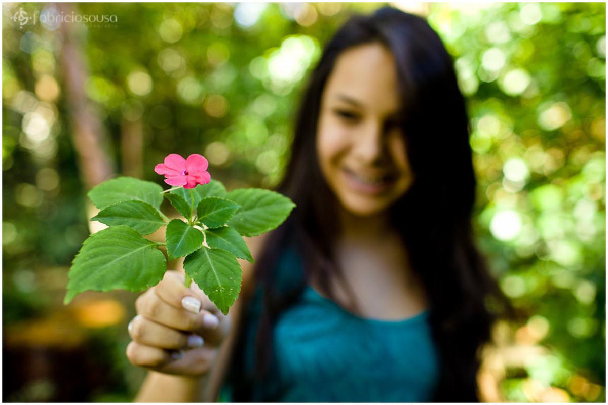 Foco na flor que a jovem de 15 anos segura