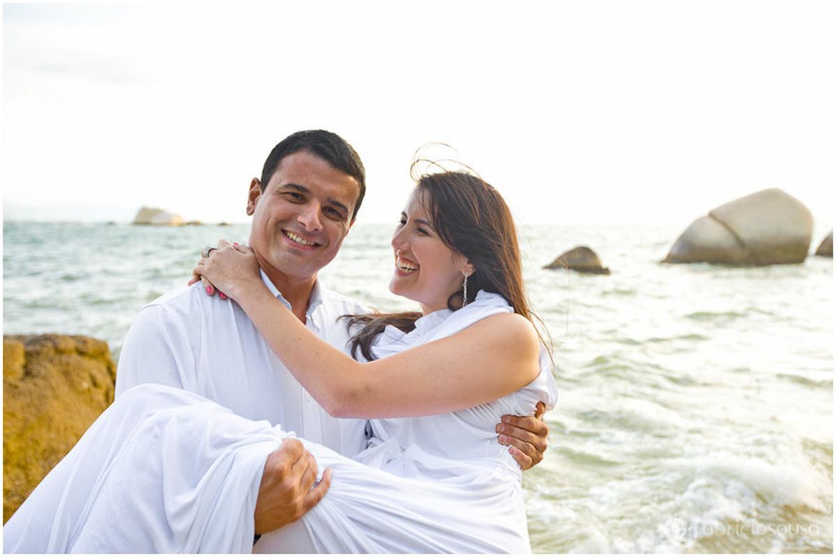 Namorado carrega namorada no colo na beira do mar