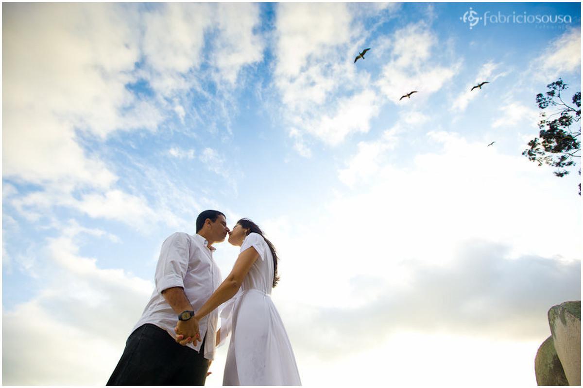 Cacau e Marcelo se beijam de mãos dadas e céu com aves e nuvens ao fundo – ensaio pré-casamento
