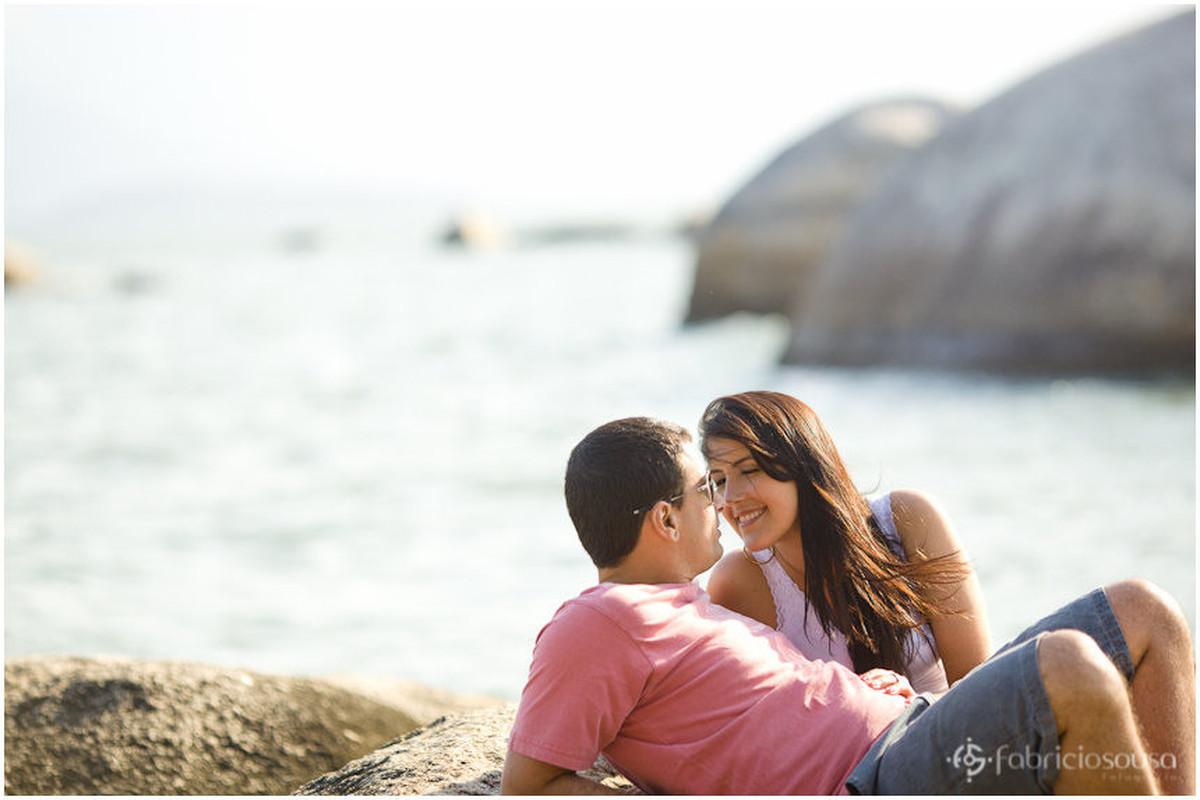 Casal paquera na pedra na beira do mar da praia