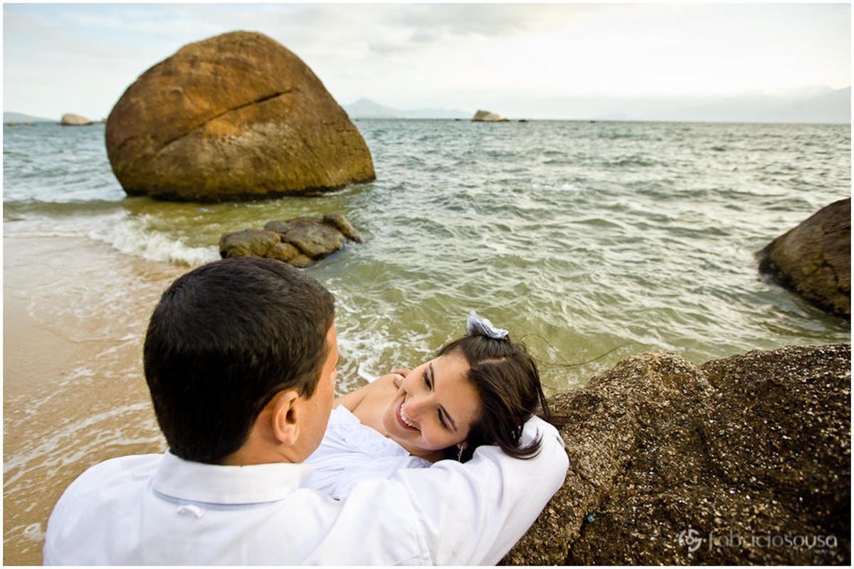 Marcelo e Cacau trocam olhares apoiados em pedra na praia na beira do mar