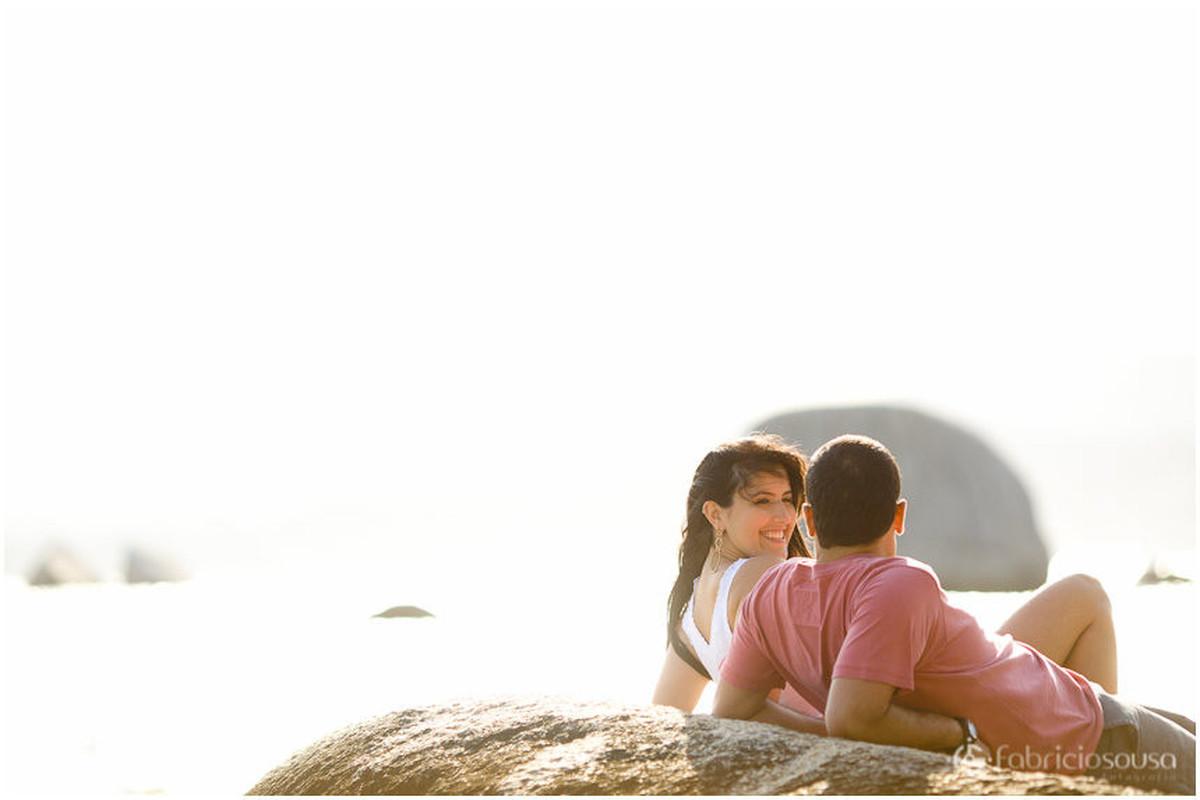 Casal de noivos aproveitam o sol escorados sobre uma pedra na beira do mar
