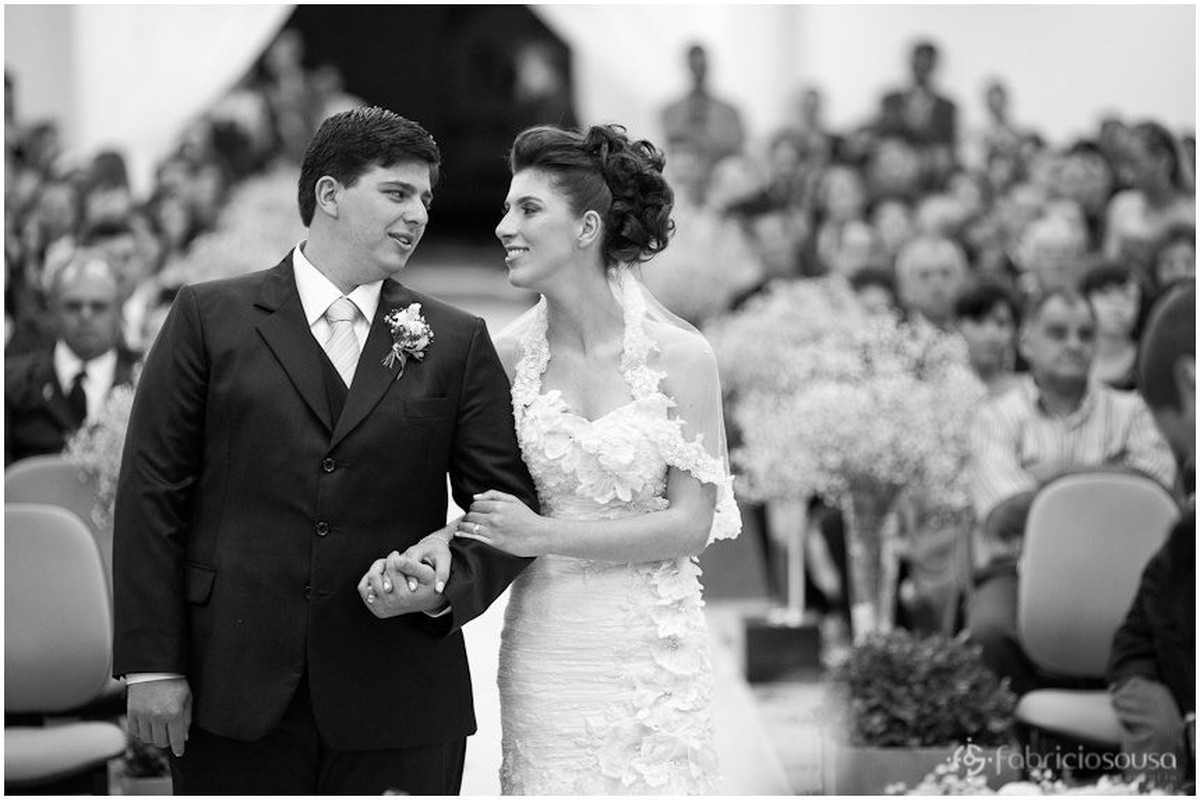 Noivo e noiva de braços dados no altar da igreja