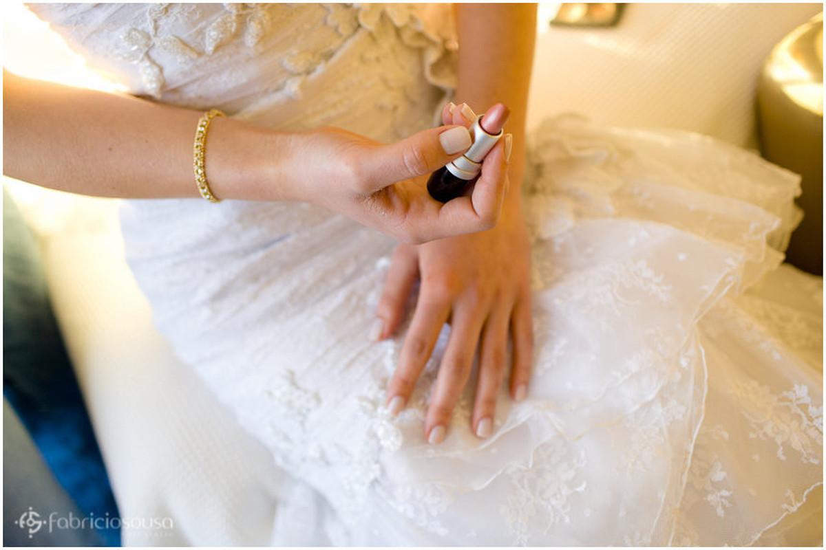 Close nas mãos da noiva segurando batom