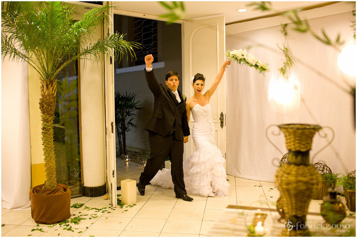 Noivo e noiva chegam à recepção dos convidados para a festa