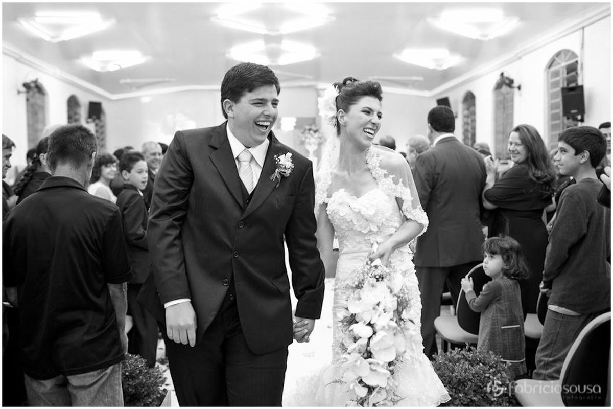 Casal de noivos sorriem alegres na saída da igreja