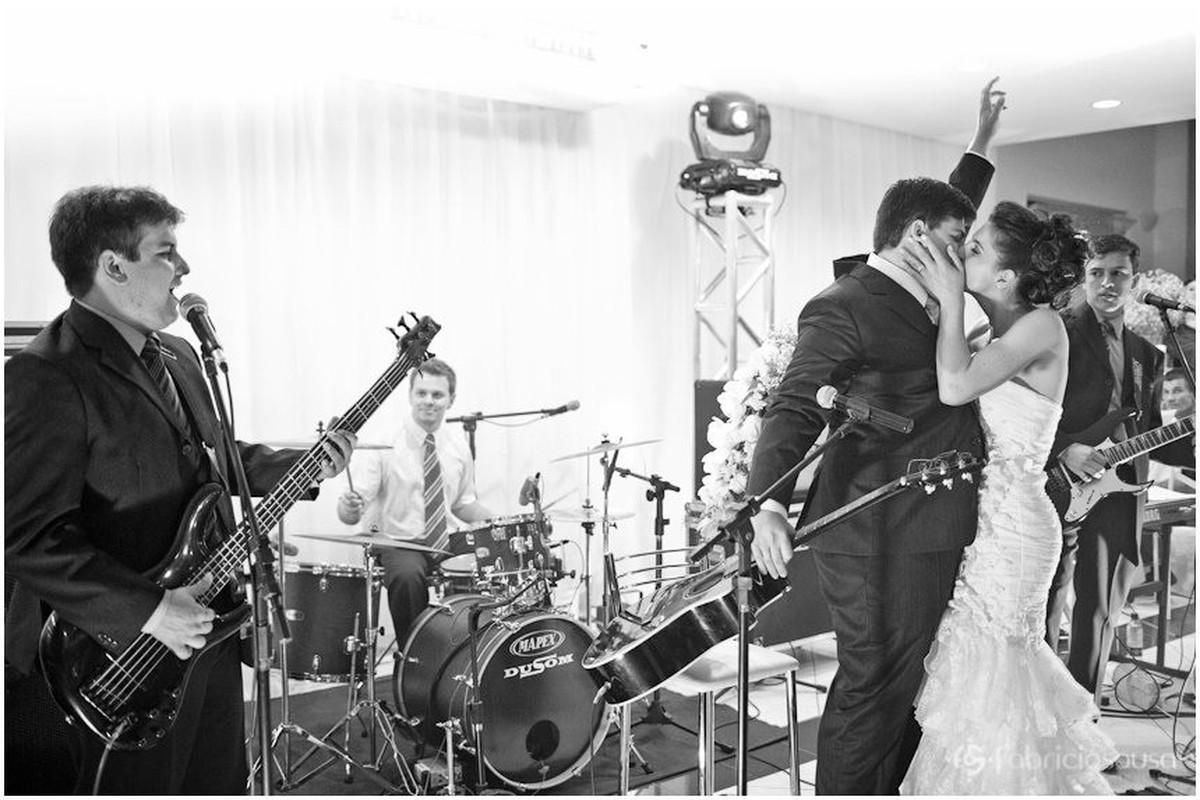 Noivos se beijam no palco em frente à banda