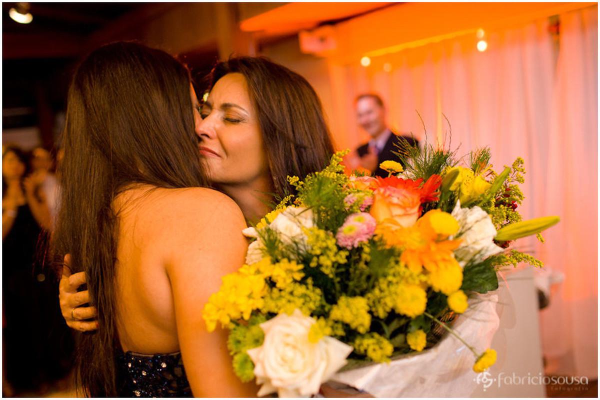 Mãe emocionada abraça e entrega bouquet de flores para a filha