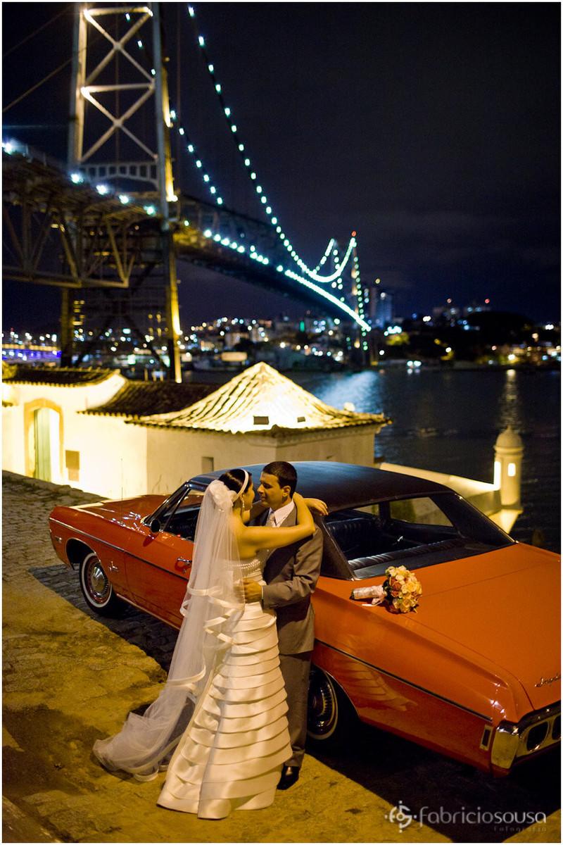 Casal de noivos posam ao lado do carro embaixo da ponte Hercilio Luz