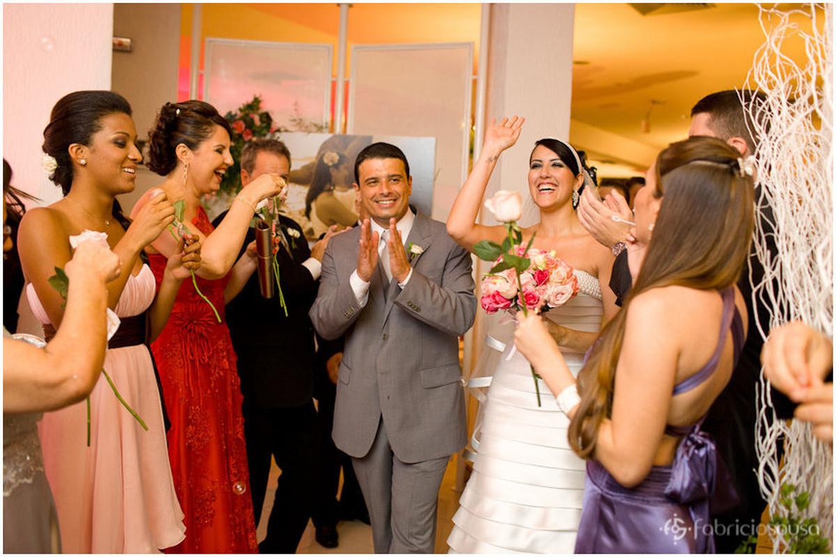 Noivo e noiva comemoram junto com parentes e padrinhos