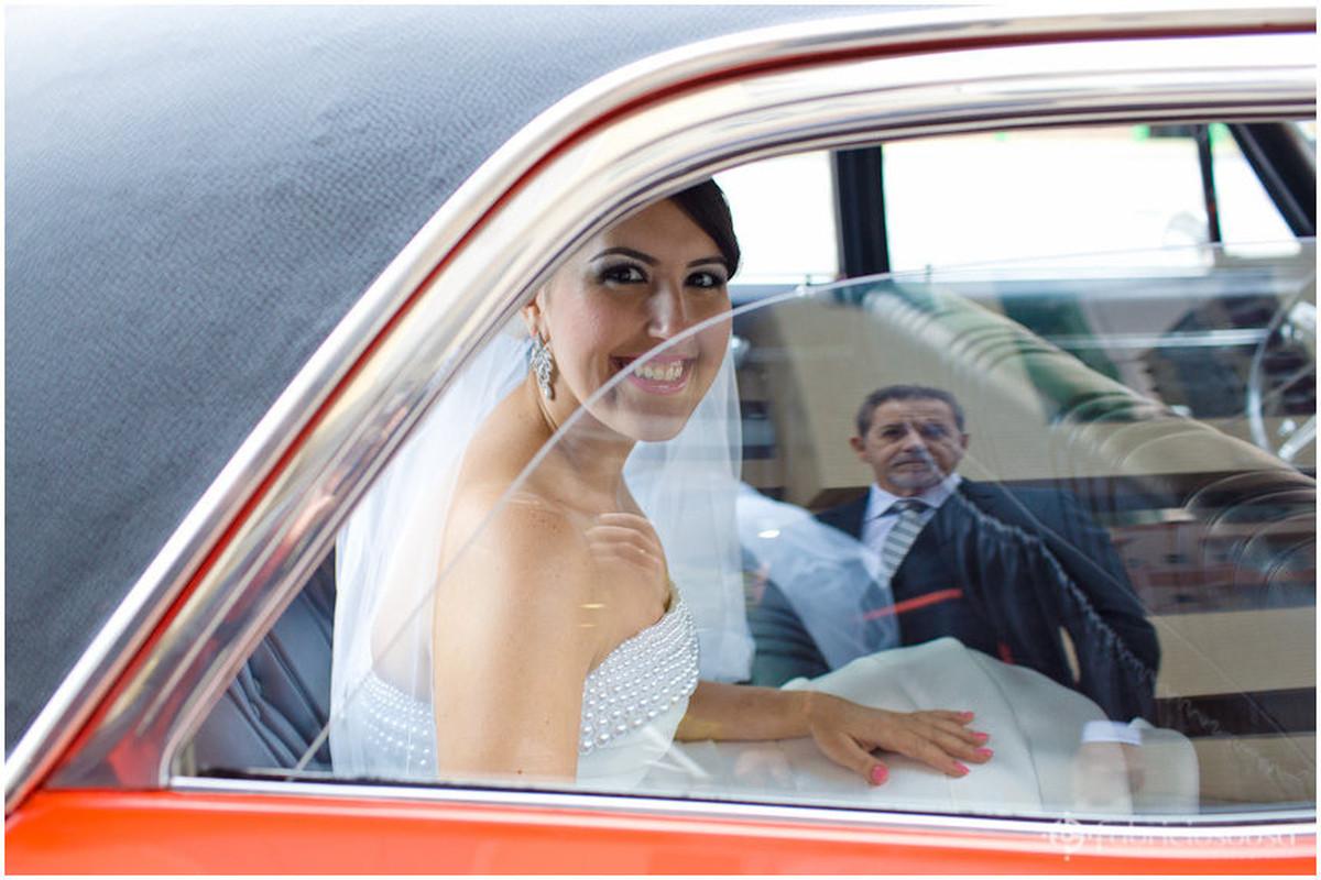 Noiva posa dentro de carro que reflete o pai no vidro