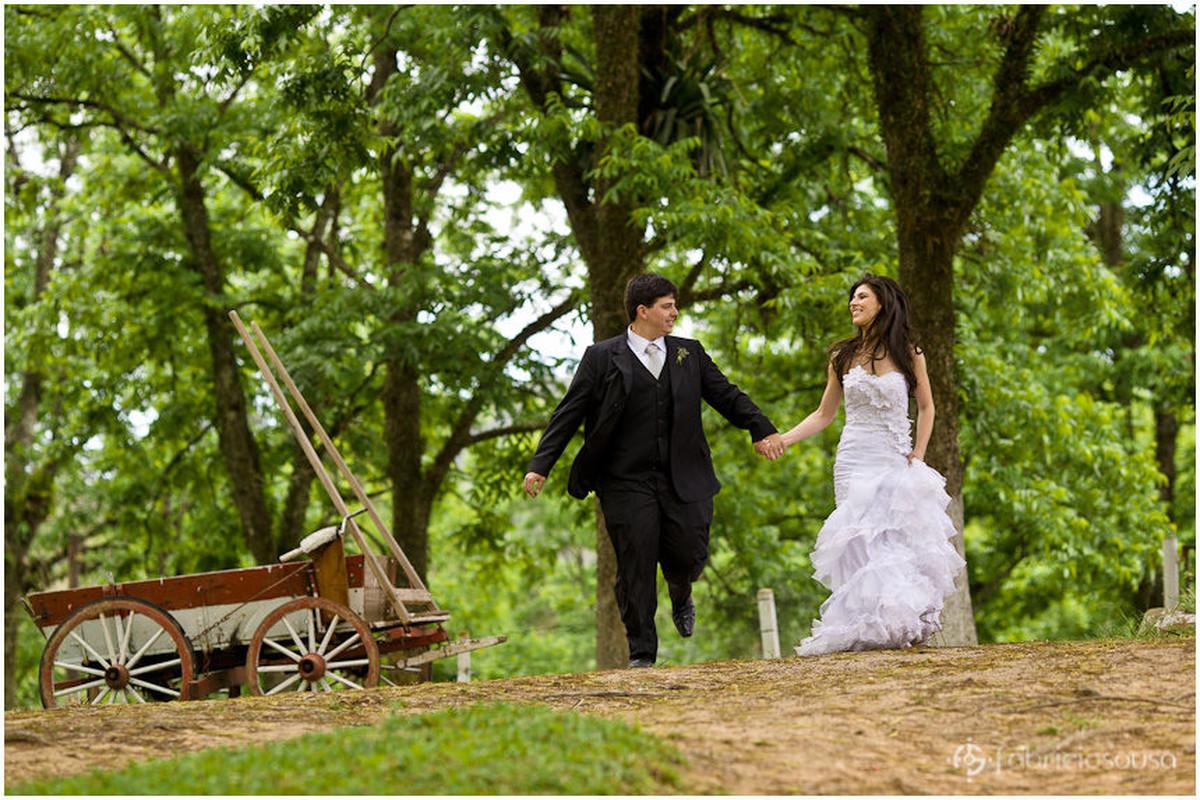 Noivos correm de mãos dadas no parque em meio à natureza