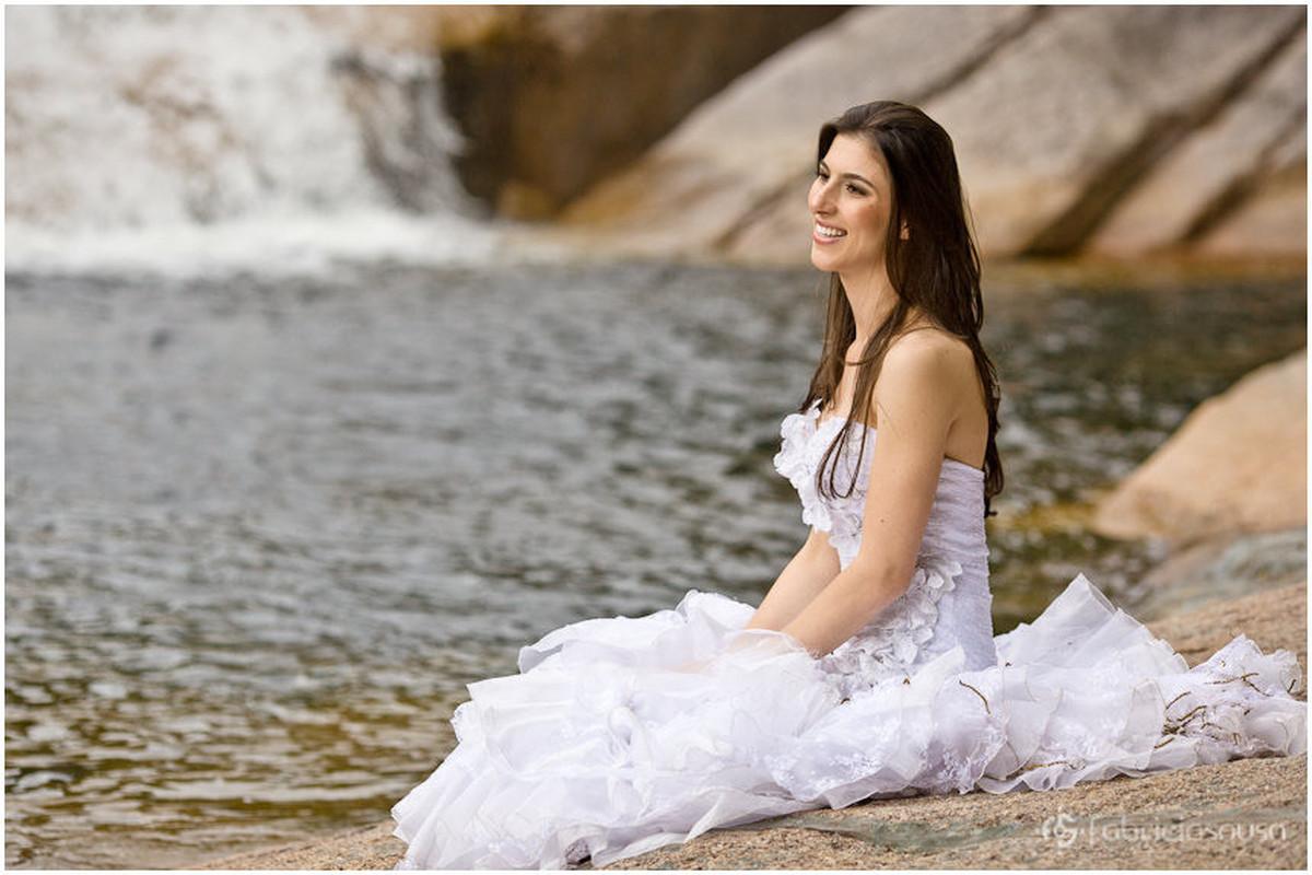 Noiva posa sentada em pedra à beira da água