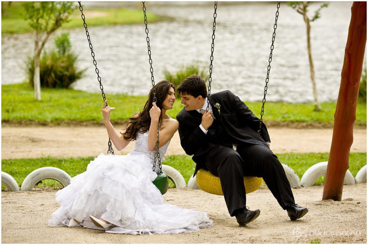 Casal de namorados se aproximam para o beijo no balanço do parque