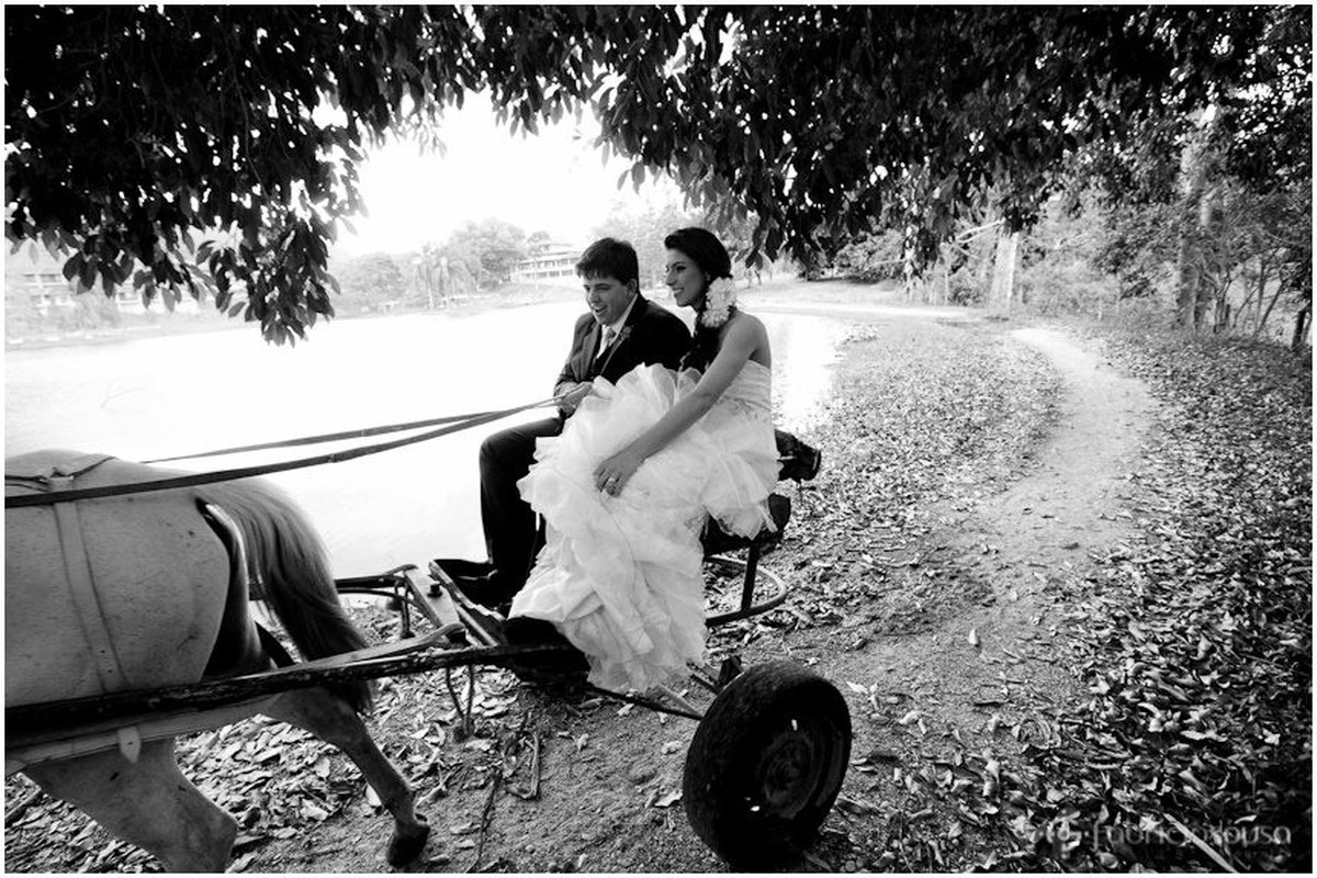 Casal de noivos sentados em charrete preto e branco
