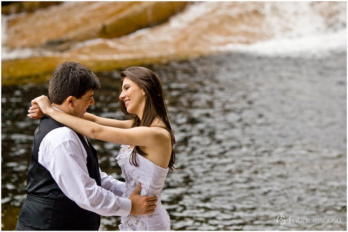 Recem casados se abraçam na beira da cachoeira