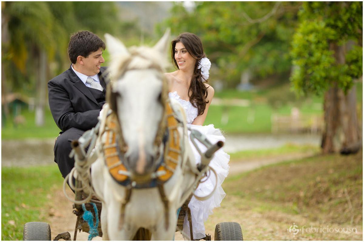 Noivo e noiva andam em charrete movida à cavalo