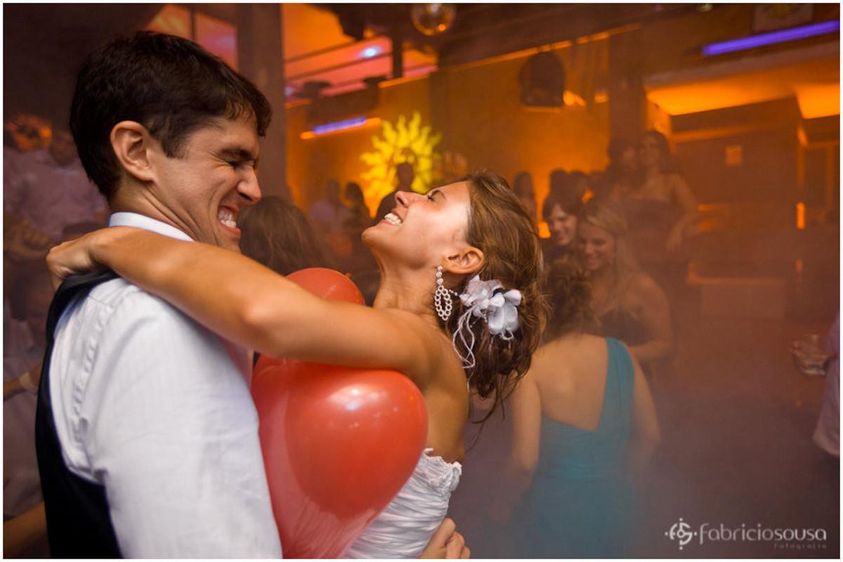 noivos tentando estourar balão de coração vermelho
